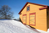 Rural yellow wooden house in winter season — Stock Photo