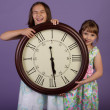 Two laughing girls holding a large wall clock — Stock Photo