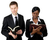 Multi-ethnic business couple reading bibles — Stock Photo