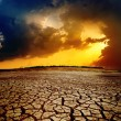 Dramatic sunset over dry cracked earth — Stock Photo #10115865