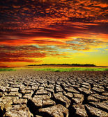 Red dramatic sunset over dry cracked earth — Stock Photo