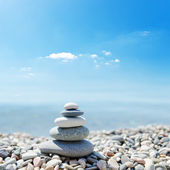Pilha de pedras do zen sobre o fundo do mar e as nuvens — Foto Stock