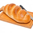Fresh bread with knife on breadboard — Stock Photo