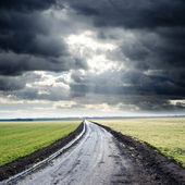 Dirty road to cloudy horizon. rain before — Stock Photo
