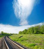 Kolejowa idzie na horyzoncie w zielony krajobraz — Zdjęcie stockowe