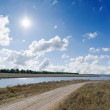 Sun on cloudy sky over rural road and river near it — Stock Photo