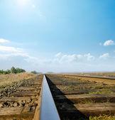 Railway to horizon under sunny sky — Stock Photo
