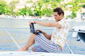 Working man with laptop sitting on white yacht, beach — Stock Photo