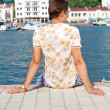 Handsome man relaxing, sitting on the pier near sea, looking awa — Stock Photo #10188728