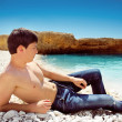 Portrait of cute young man on the beach, blue sky — Stock Photo