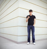 Handsome student using a mobile phone with perspective wall copyspace — Stock Photo