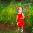 Happy smiling little fun girl in red dress with flower in hand, green outdoors — Stock Photo