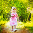 Happy funny little girl walking on road, nature outdoors — Stock Photo