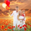Happy family on  Field of poppies spring flowers, sunset outdoors — Stock Photo