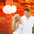 Happy couple embracing over poppies field and sunset, holding bunch of balloons — Stock Photo