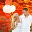Stock Photo: Happy couple embracing over poppies field and sunset, holding bunch of balloons