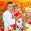 Happy family on poppies flowers field, sunset outdoors — Stock Photo