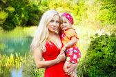 Joven madre con el niño muy sonriente, fuera de retrato — Foto de Stock
