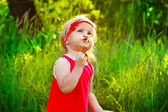 Outdoors Portrait of funny lovely little girl in red dress — Stock Photo
