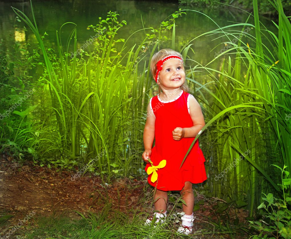 Happy smiling little fun girl in red dress with flower in hand, green outdoors — Stock Photo #10652616