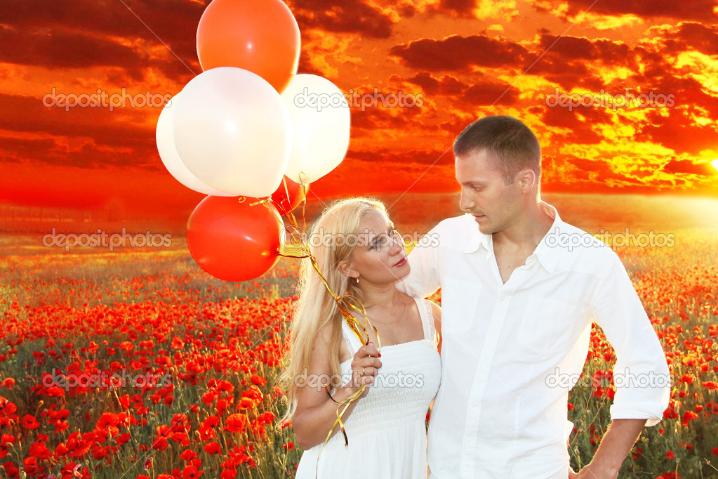 Happy couple embracing over poppies field and sunset, holding bunch of balloons — Stock Photo #10652634