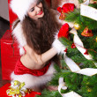 Royalty-Free Stock Photo: Young woman decorating Christmas tree in Santa clothes