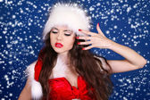 Girl in Santa Claus red dress posing on snow background — Stock Photo