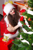Young woman decorating Christmas tree in Santa clothes — Stock Photo