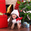 Home, woman in Santa suit lying near Christmas tree and gift — Stock Photo