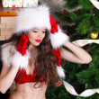 Beautiful sexy girl wearing santa claus clothes in interior — Stock Photo