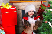 Happy smiling girl with red gloves near Christmas decoration — Stockfoto