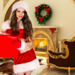 Girl with gift near Christmas-tree decorations in comfortable in - Stockfoto
