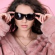 Foto Stock: Photo of sexual beautiful girl is in fur clothes over pink