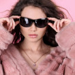 Photo of sexual beautiful girl is in fur clothes over pink - Stock Photo