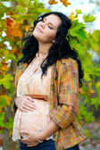 Pregnant woman caressing her belly, outdoors — Stock Photo