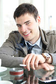 Closeup portrait of a happy young man with cigarette — Stock Photo