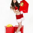 Beautiful young woman in Santa Claus clothes over Christmas back — Stock Photo