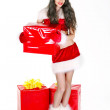 Girl in Santa clothes holding many Christmas gifts in her arms i — Stock Photo