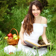 Smiling beautiful woman read the book on the nature. garden — Stock Photo #8383167