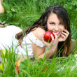Happy smiling young women with red apple on the green field, out — Stock Photo #8383175