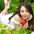 Satisfied young women with red apple on the green field, outdoor — Stock Photo