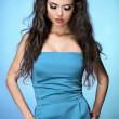 Young sexy brunette model girl posing over blue background — Stock Photo #8401353