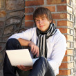 Young man with laptop leaning against the brick wall — Stock Photo