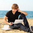 Casual young business man using laptop on the beach — Stockfoto