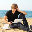 Casual young business man using laptop on the beach — Stok fotoğraf