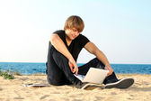 Young student man using laptop on the beach — Stock Photo