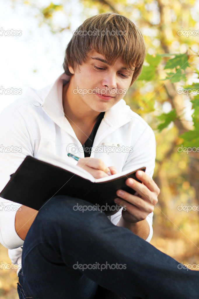 Man writing on His Organizer on a Bench Outdoors — Stock Photo #8611836