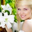 Happy Smiling blonde young woman with white lily, nature — Stock Photo #8994334