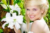 Gelukkig lachend blonde jonge vrouw met witte lelie, natuur — Stockfoto