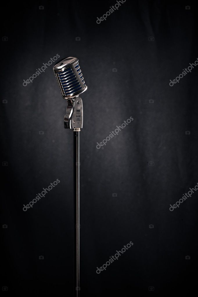 Microphone with stand in spotlight over black curtain — Stock Photo #10429587